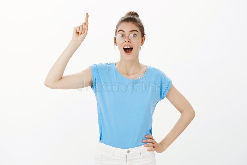 我有优良创艺 蓝色T恤杉的活跃悦目女学生,握在臀部的手和举食指 免版税库存图片