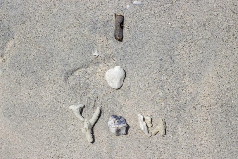 我爱你写在珊瑚、壳和棍子在沙子作为爱消息为灵魂伴侣 免版税库存图片