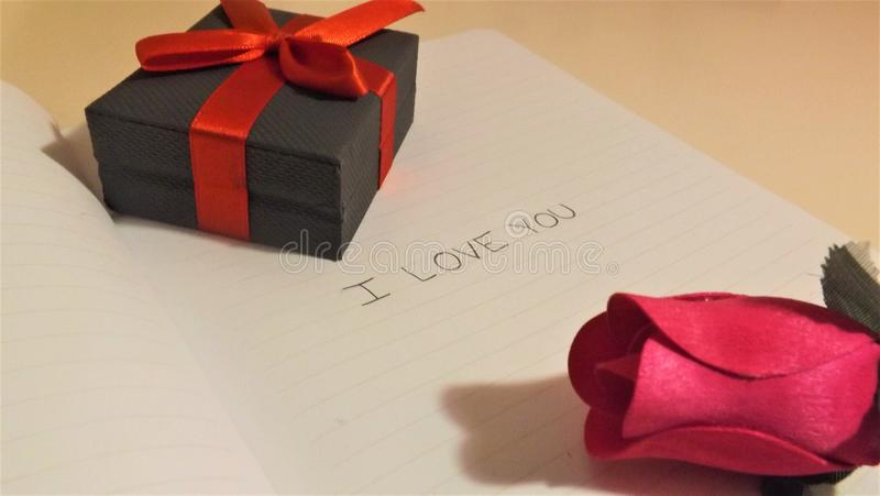 我爱你在有铅笔和箱子的笔记本 图库摄影