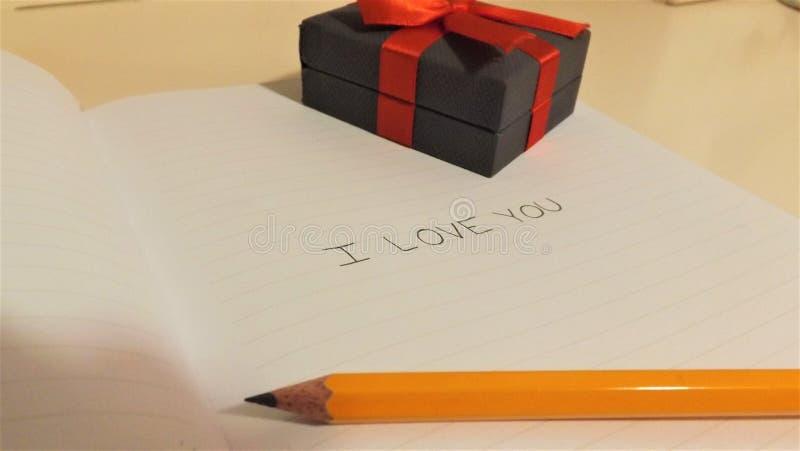 我爱你在有铅笔和箱子的笔记本 免版税库存照片