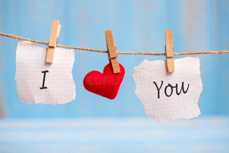 我爱你在纸和红心垂悬在与拷贝空间的线的形状装饰的词在蓝色木背景的文本的 爱, 库存照片