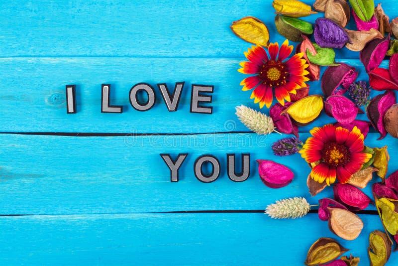 我爱你在蓝色木头的文本与花 库存图片
