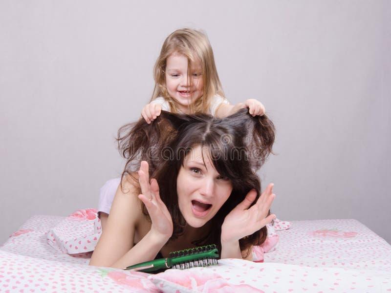 我的女儿拉扯她的头发妈妈 免版税库存照片
