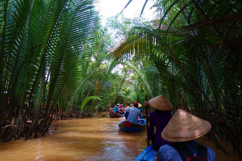 我的Tho,越南:湄公河三角洲密林巡航的游人与在洪水泥的未认出的craftman和渔夫划艇 库存照片