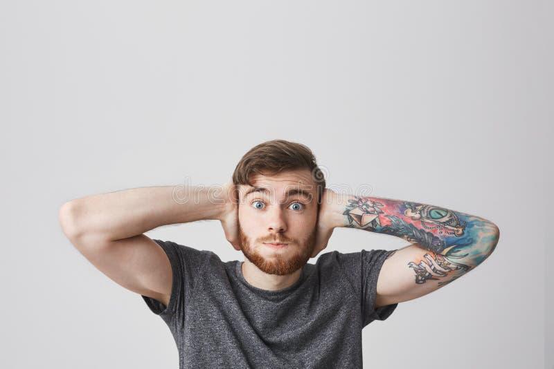 我穿上` t听见任何东西 有时兴的发型的可爱的滑稽的有胡子的人和被刺字的胳膊闭合值的耳朵用手 免版税库存图片