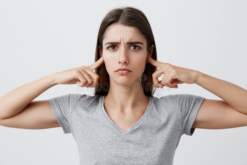 我穿上` t要再听您 有长的棕色头发的雍美丽的不快乐的白种人女孩在灰色衬衣衣物 免版税图库摄影
