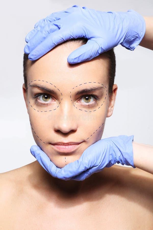 我要美丽!一名妇女的头在一位整形外科医生的手上 库存照片