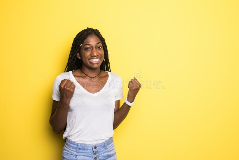 我赢得了 庆祝赢得的成功愉快的非洲的妇女是黄色演播室背景的一个优胜者 胜利,欢欣概念 ?? 免版税图库摄影