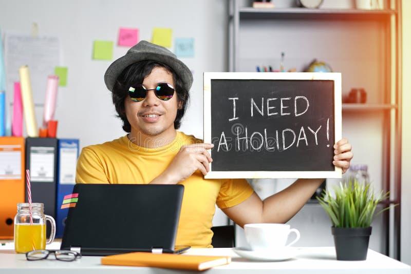 我需要假日概念 拿着黑板的年轻人,当Wor时 图库摄影