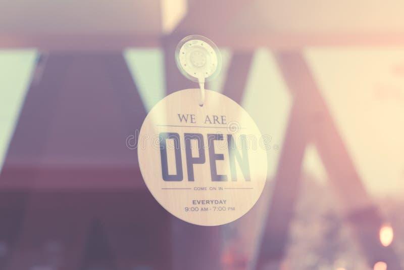 我们是开放的开放标志宽广在玻璃门被过滤的图象被处理的葡萄酒作用 免版税库存照片