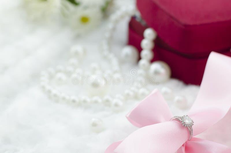 钻戒和桃红色丝带在珍珠项链背景 免版税库存照片