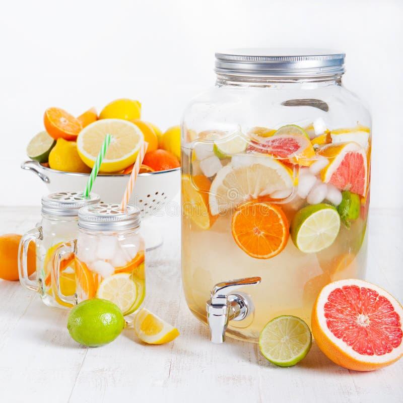 戒毒所果子灌输了调味的水,柠檬水,在一台饮料分配器的鸡尾酒用新鲜水果 库存照片