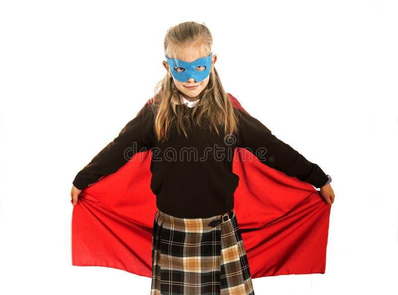 7或8岁在白色后面在校服执行愉快和激动隔绝的特级英雄服装的年轻女孩 免版税库存照片