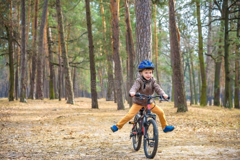 3或5年的愉快的孩子男孩获得乐趣在有一辆自行车的秋天森林在美好的秋天天 活跃儿童佩带的自行车盔甲 库存图片
