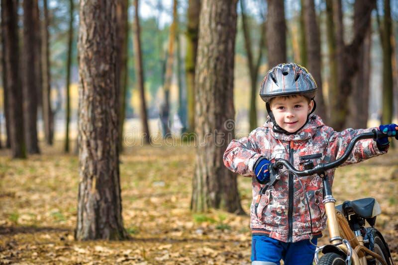 3或5年的愉快的孩子男孩获得乐趣在有一辆自行车的秋天森林在美好的秋天天 活跃儿童佩带的自行车盔甲 免版税库存照片