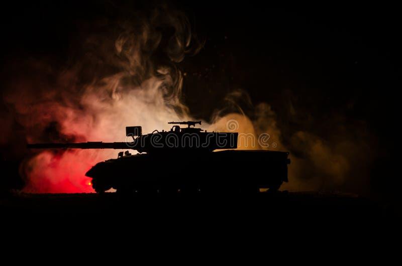 战争概念 与在战争雾天空背景,在行动的德国坦克的军事剪影场面战斗在多云地平线下在晚上 A 库存图片