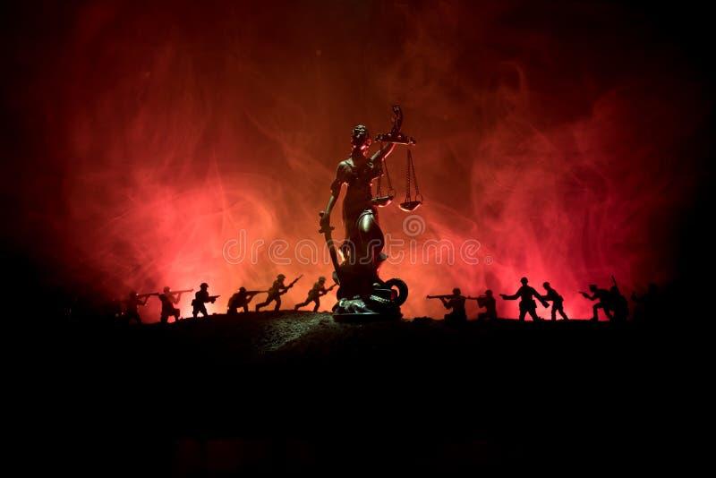 战争没有正义概念 与场面和正义战斗的雕象在黑暗的被定调子的有雾的背景的军事剪影 免版税图库摄影