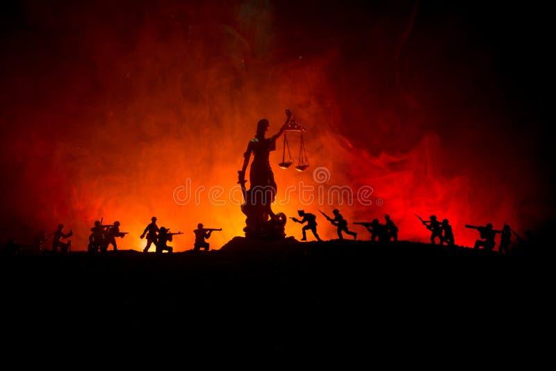 战争没有正义概念 与场面和正义战斗的雕象在黑暗的被定调子的有雾的背景的军事剪影 免版税库存照片