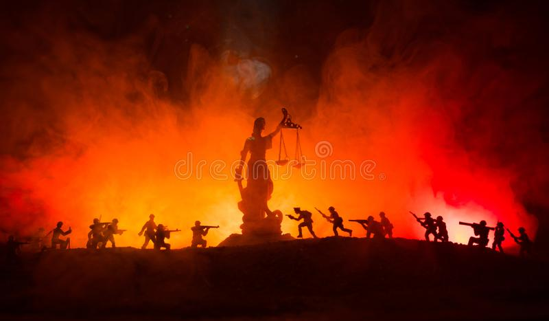 战争没有正义概念 与场面和正义战斗的雕象在黑暗的被定调子的有雾的背景的军事剪影 免版税库存图片