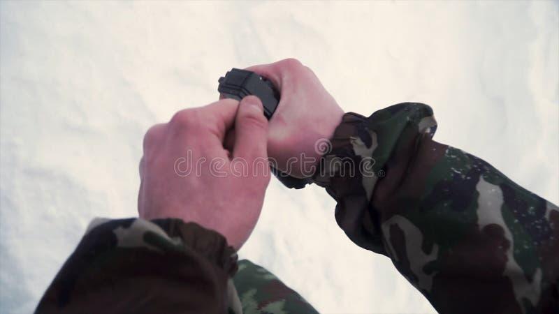 战士在他的手上拿着训练手榴弹,当通过在军队,雪背景时的军事演习 夹子 A 免版税库存照片