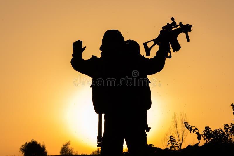 战士日落在制服蹲下了 库存图片