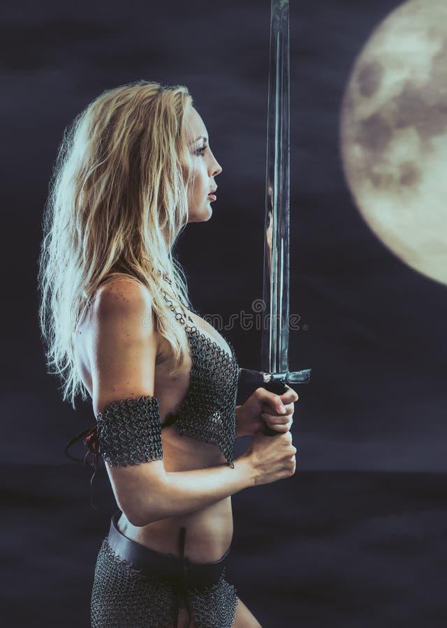 战士有一把剑的北欧海盗女孩在手上 库存照片