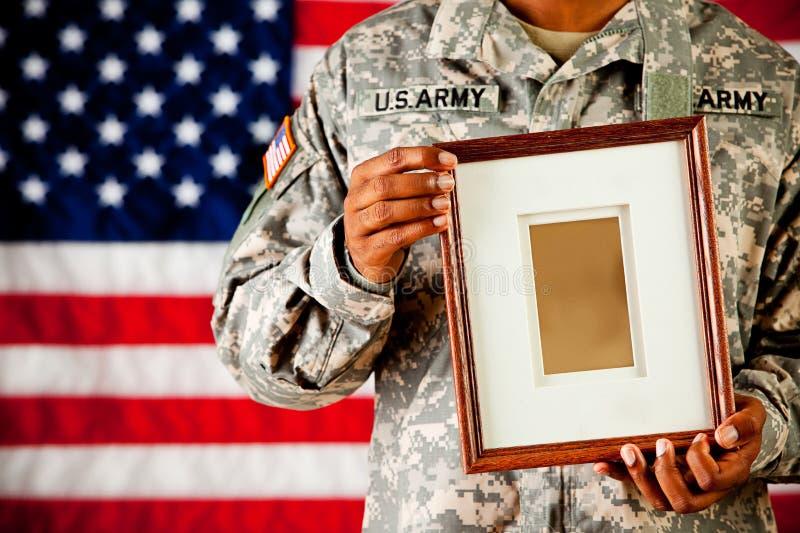 战士:拿着en空的画框 库存图片