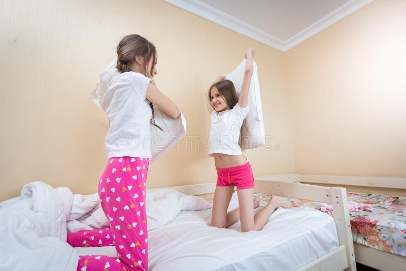 战斗与在床上的枕头的两个美丽的女孩在卧室 免版税库存照片
