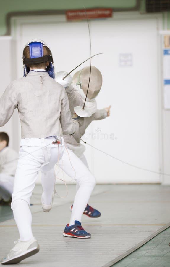 战斗与在操刀的比赛的双刃剑的两个少年击剑者 库存照片