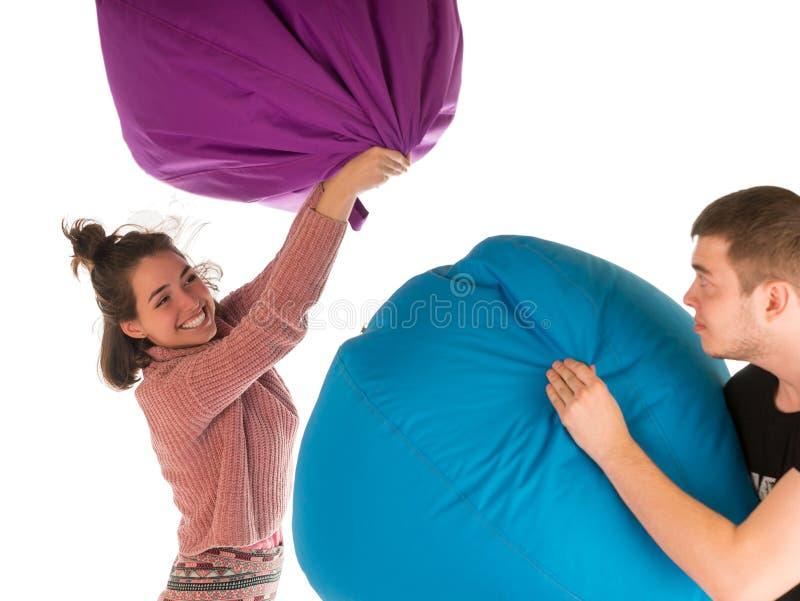 战斗与装豆子小布袋椅子的年轻滑稽的夫妇 免版税库存照片
