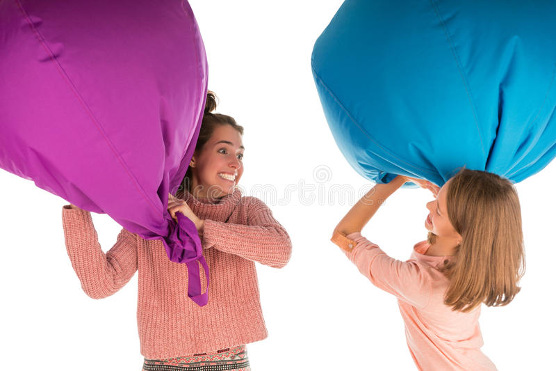 战斗与装豆子小布袋椅子的年轻滑稽的笑的女孩 免版税库存照片