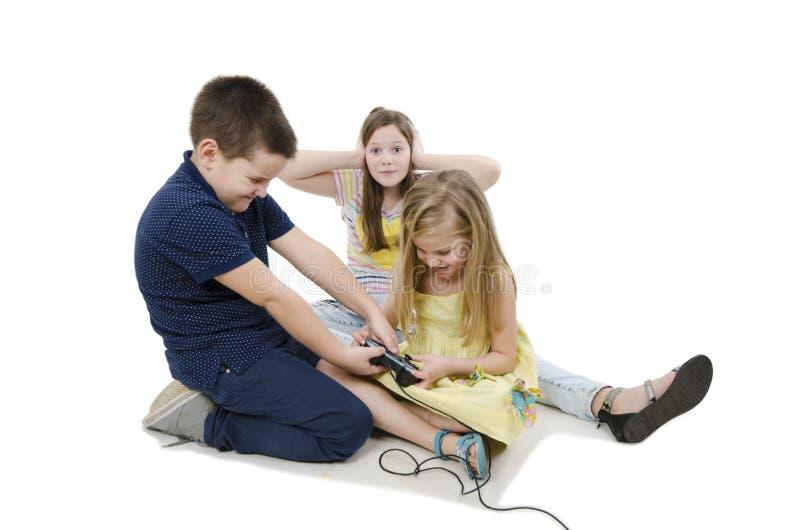 战斗为电子游戏的两个孩子 盖她的耳朵的懊恼老姐妹用她的手不能听 免版税库存图片