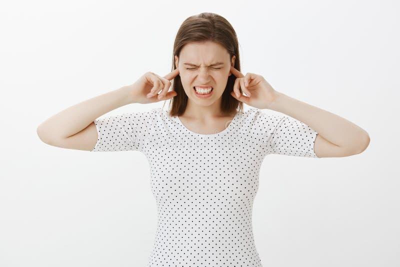 战斗做鬼脸的父母再的女孩皱眉和,握紧牙,当设法关闭有食指的时耳朵 免版税库存图片