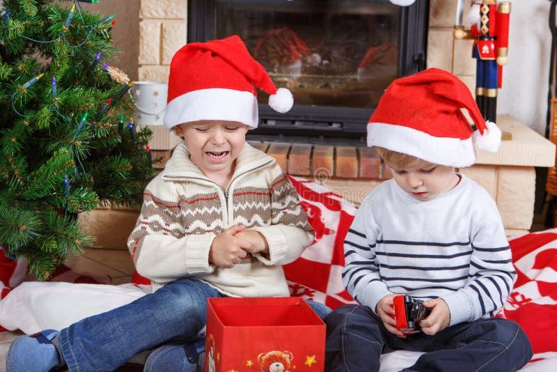 战斗关于圣诞节礼物的两个小兄弟姐妹男孩 免版税库存照片