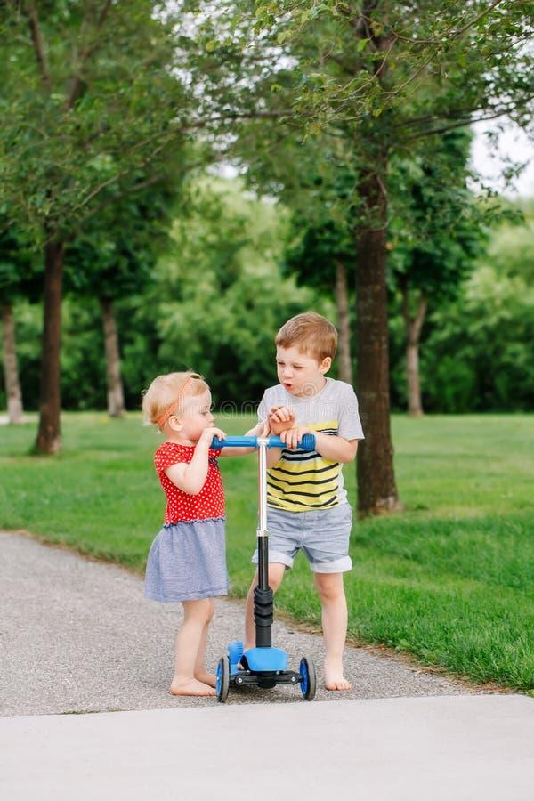 战斗在公园的两个一点白种人学龄前孩子外面 男孩和女孩不可能分享一辆滑行车 库存图片