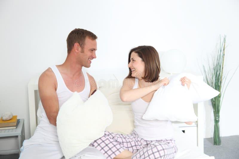 战斗在床上的笑的年轻夫妇枕头 图库摄影