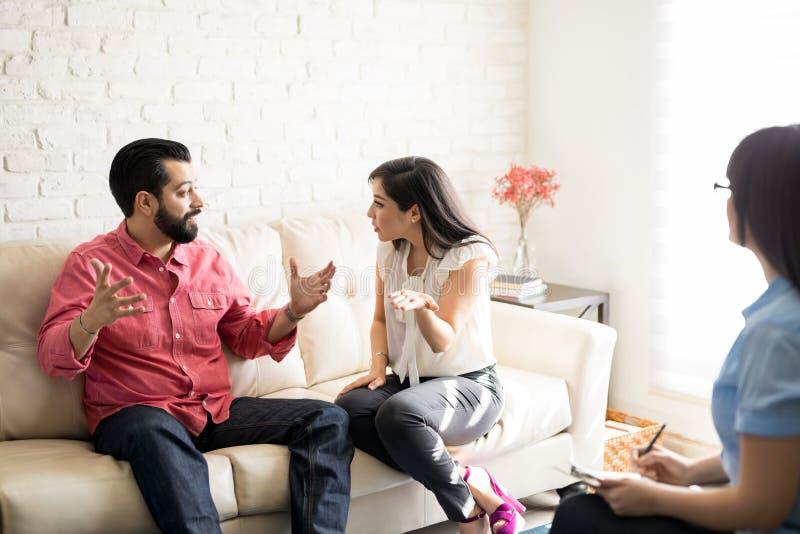 战斗在心理学家前面的不快乐的夫妇 免版税库存图片