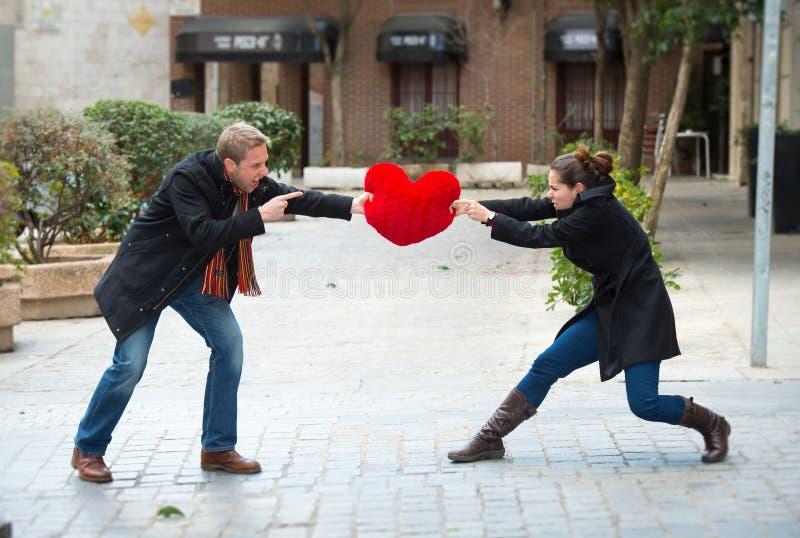 战斗在爱心脏的有吸引力的夫妇把枕在 免版税库存照片