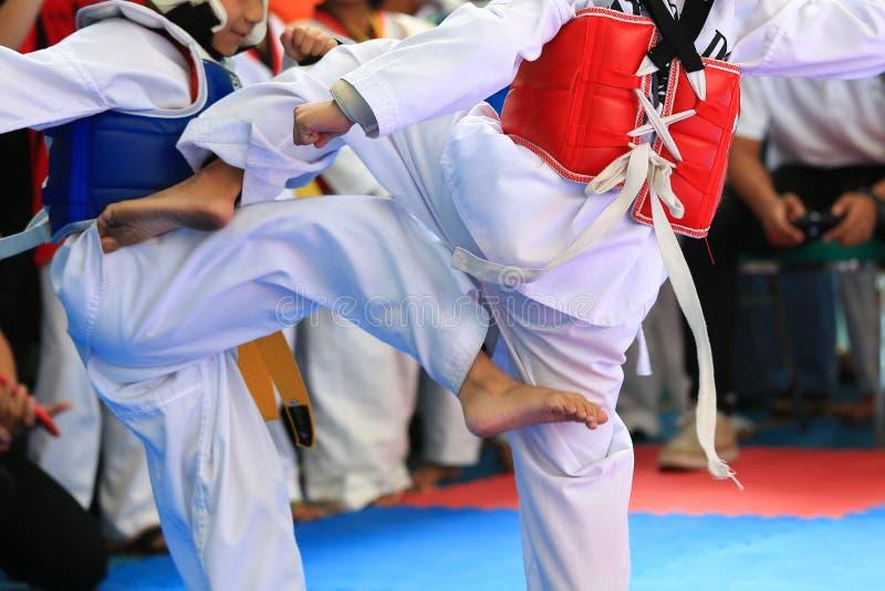 战斗在阶段的孩子在跆拳道比赛期间 免版税库存照片