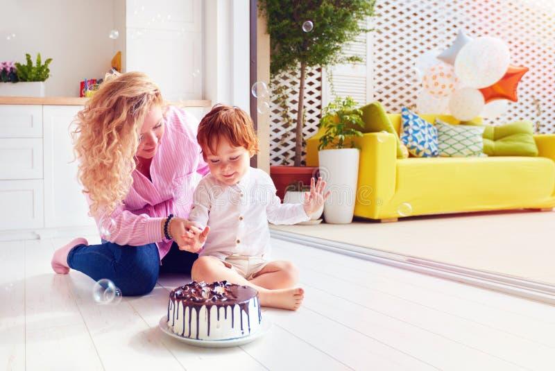 戳在生日蛋糕的愉快的母亲和小孩儿子手指 图库摄影