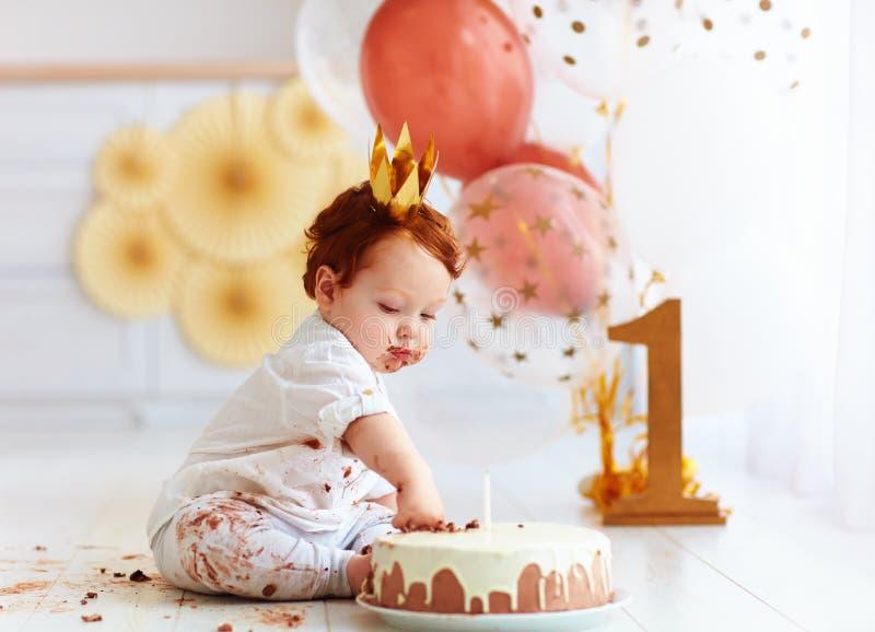 戳在他的第一生日蛋糕的好奇滑稽的男婴手指 免版税图库摄影