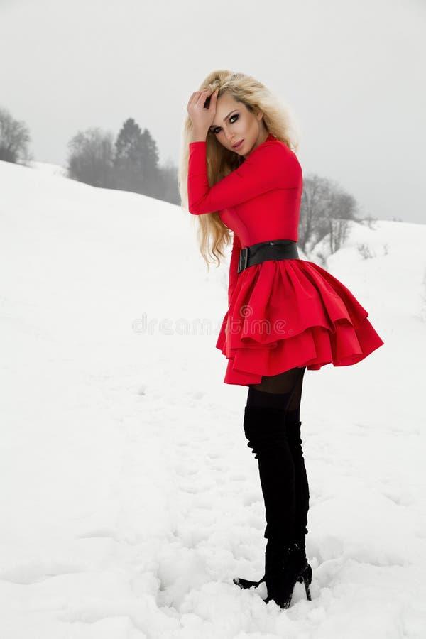 戴一件红色礼服和一个圣诞老人` s帽子在山和雪的美丽的性感的白肤金发的妇女 免版税库存照片