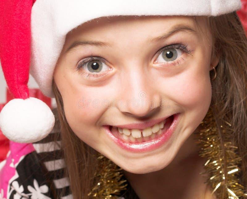 戴一件红色礼服和一个红色圣诞老人帽子的女孩 库存图片
