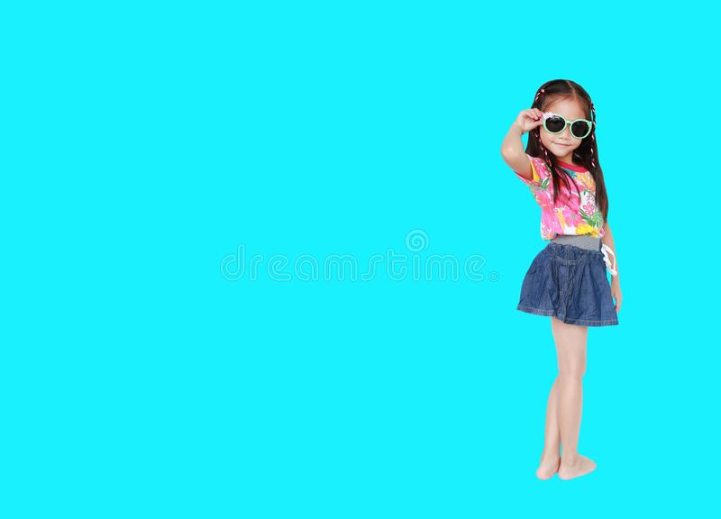 戴一件花卉样式夏天礼服和太阳镜的可爱的矮小的亚裔儿童女孩隔绝在与拷贝空间的深蓝背景 库存例证