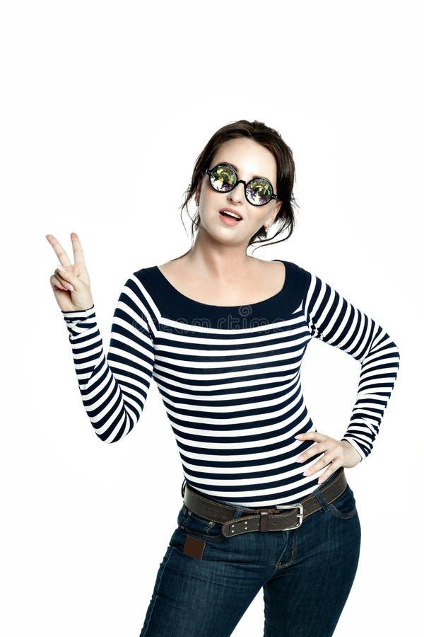 戴万花筒眼镜的女孩在一件镶边紧的女衬衫的显示和平的迹象 免版税图库摄影