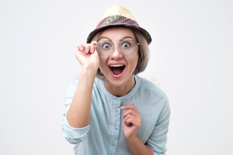 戴俏丽的夏天帽子和太阳镜的年轻美女张在惊奇的嘴 免版税图库摄影
