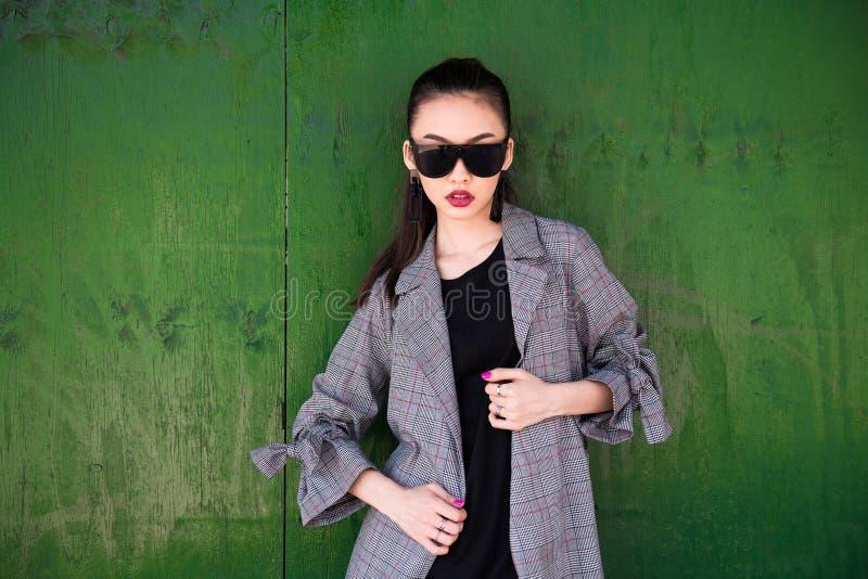 戴偶然成套装备和太阳镜的美丽的时兴的亚裔女孩摆在对绿色木墙壁 免版税库存图片