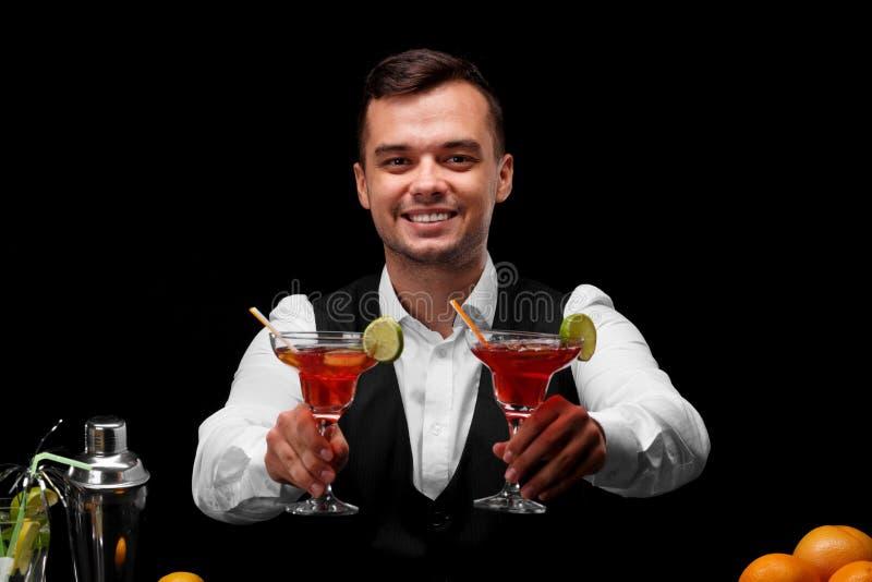 戴充分两副玛格丽塔酒眼镜的一位可爱的侍酒者鸡尾酒,桔子,柠檬,在黑背景的一台振动器 免版税库存照片