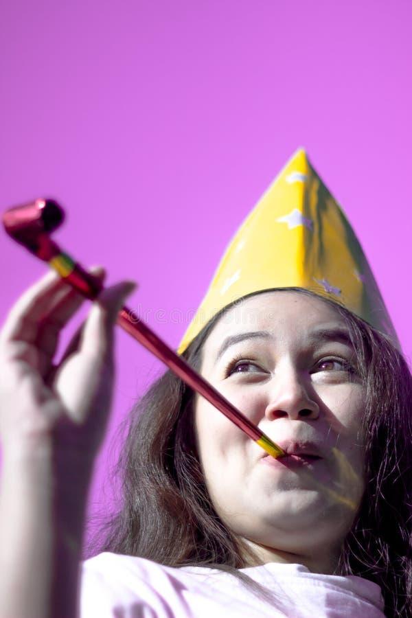 戴党帽子的可爱的少妇欢呼和庆祝吹的党垫铁 吹在党口哨a的滑稽的可爱的女孩 免版税库存照片