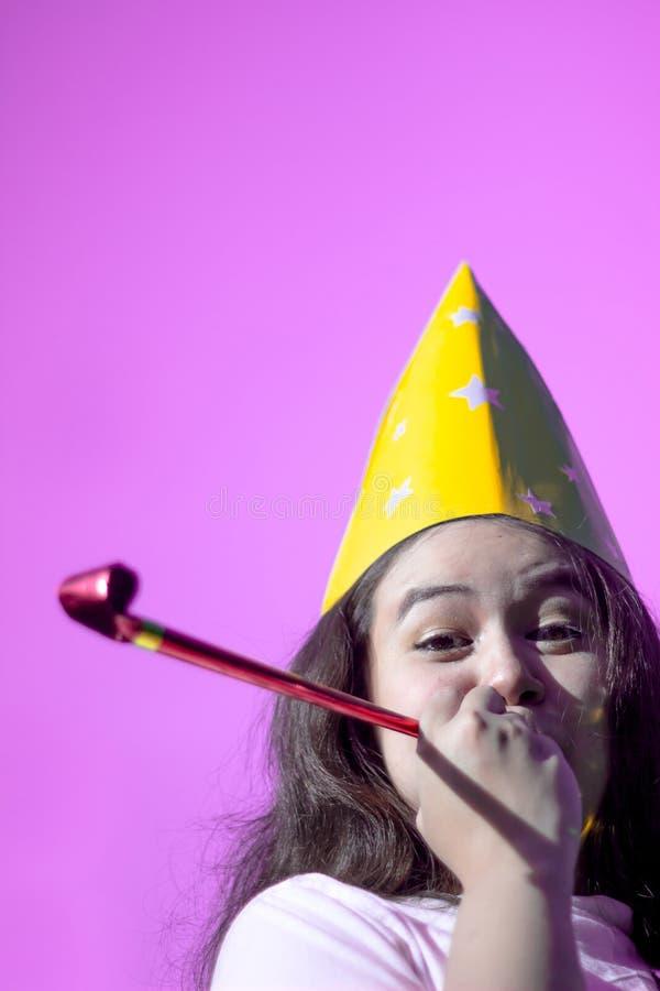 戴党帽子的可爱的少妇欢呼和庆祝吹的党垫铁 吹在党口哨a的滑稽的可爱的女孩 免版税库存图片